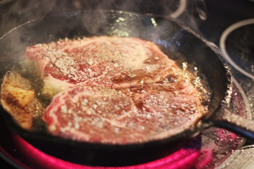 steaks cooking in a skillet