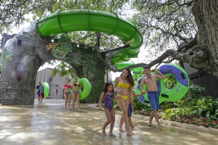 family walking in front of a green waterslide