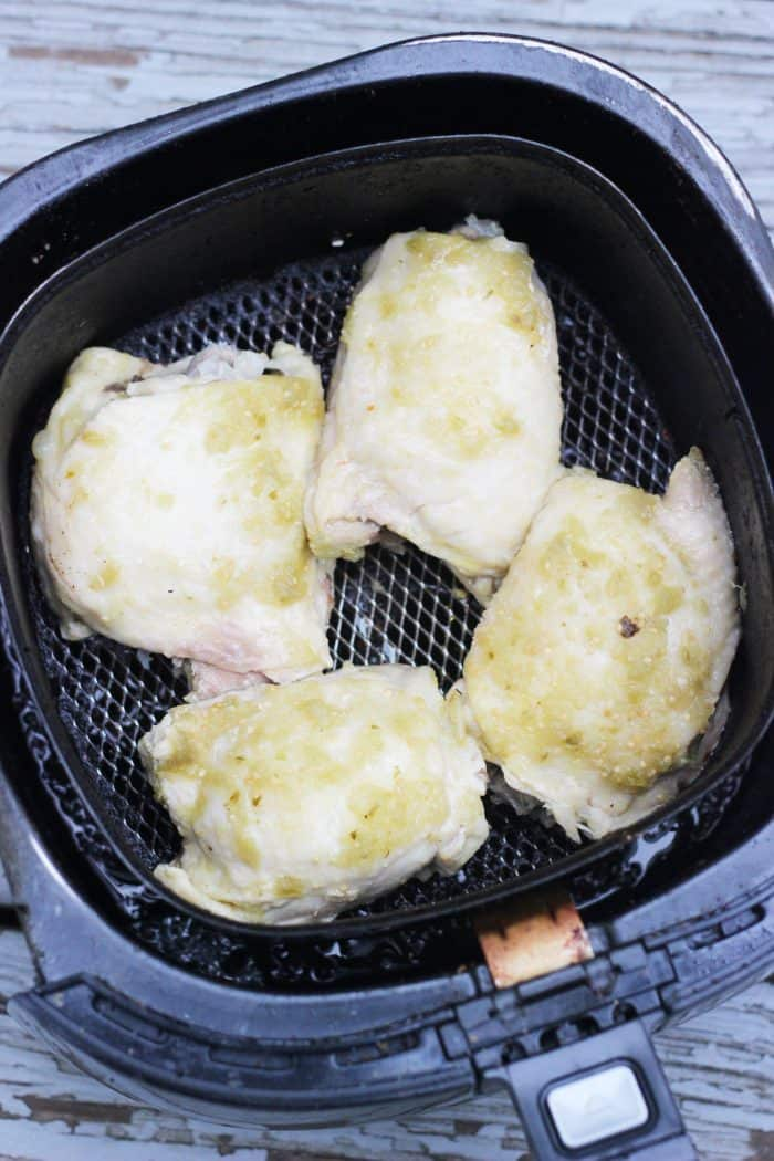 pressure cooked chicken thighs in an air fryer basket
