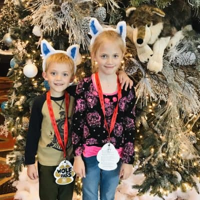 kids wearing christmas wolf ears standing in front of great wolf lodge christmas tree