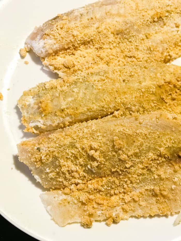 raw tilapia breaded with almond flour mixture