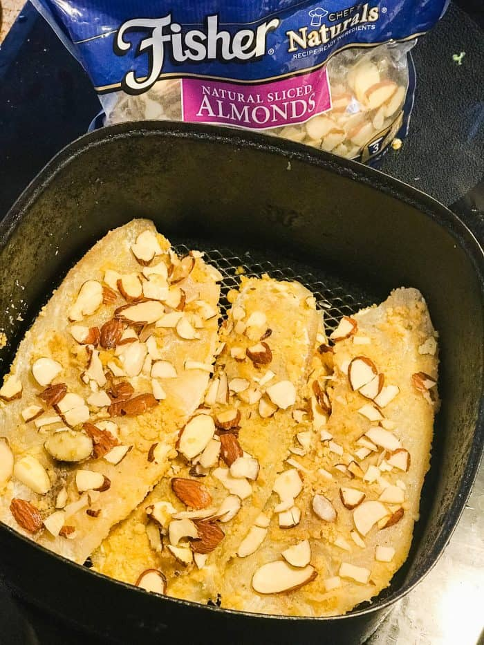raw tilapia coated in almond flour mixture and sliced almonds in air fryer basket