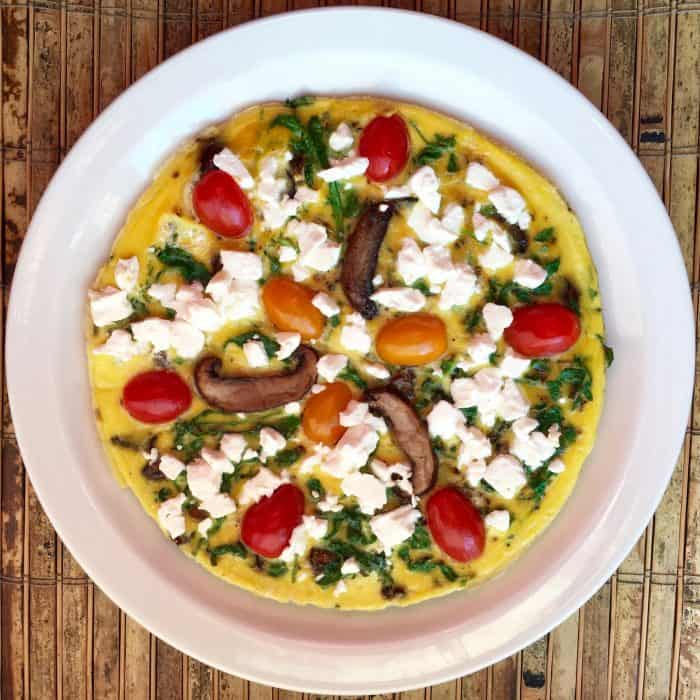 keto frittata recipe with mushrooms and goat cheese on a white plate