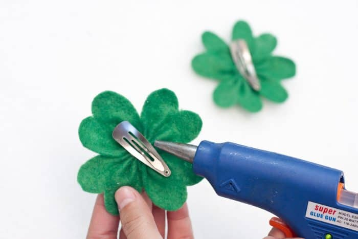 hot gluing a hair clip onto the back of the felt shamrock