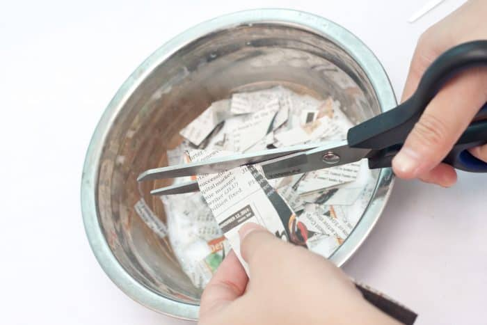 cutting strips of newspaper for paper mache easter eggs