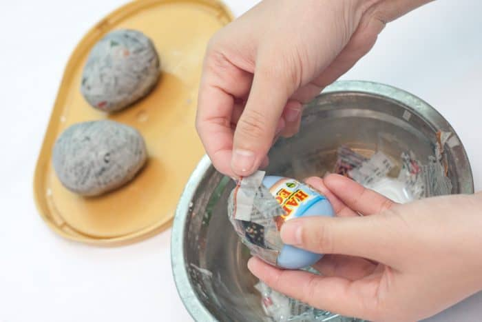 covering plastic easter eggs with wet newspaper strips