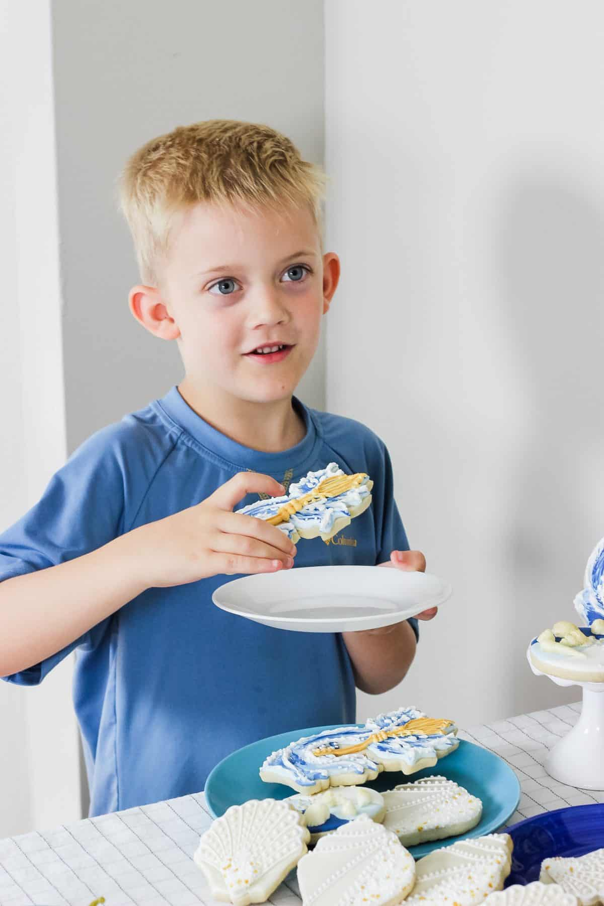 child eating a trident cookie at a percy jackson birthday party