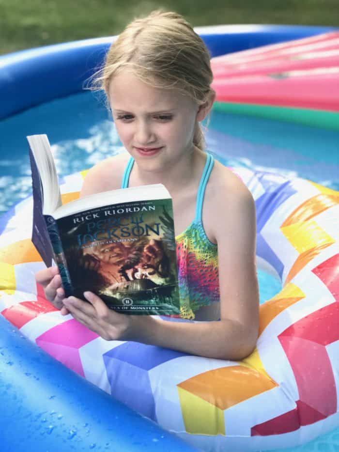 girl floating in a pool reading a percy jackson book