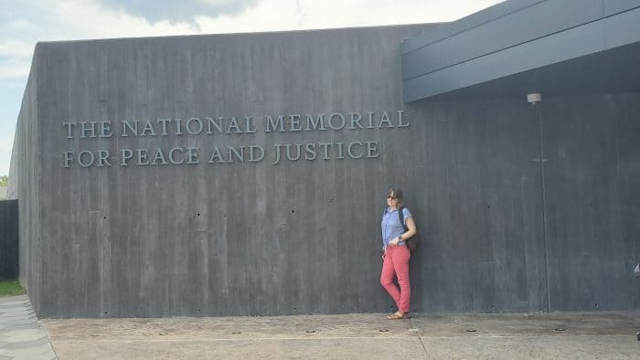 standing beneath the national memorial for peace and justice sign
