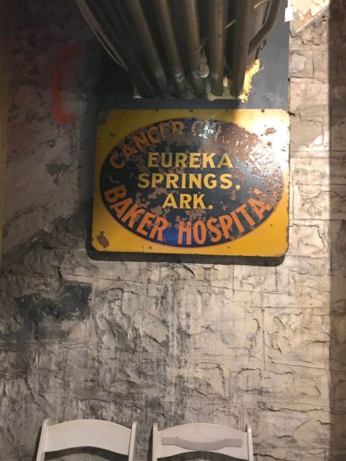 """A rusted metal sign in the basement of the crescent hotel that reads """"cancer center baker hospital eureka springs Arkansas."""""""