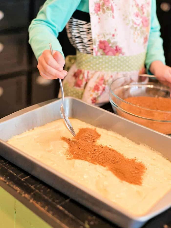 Adding cinnamon to Honey Bun Cake