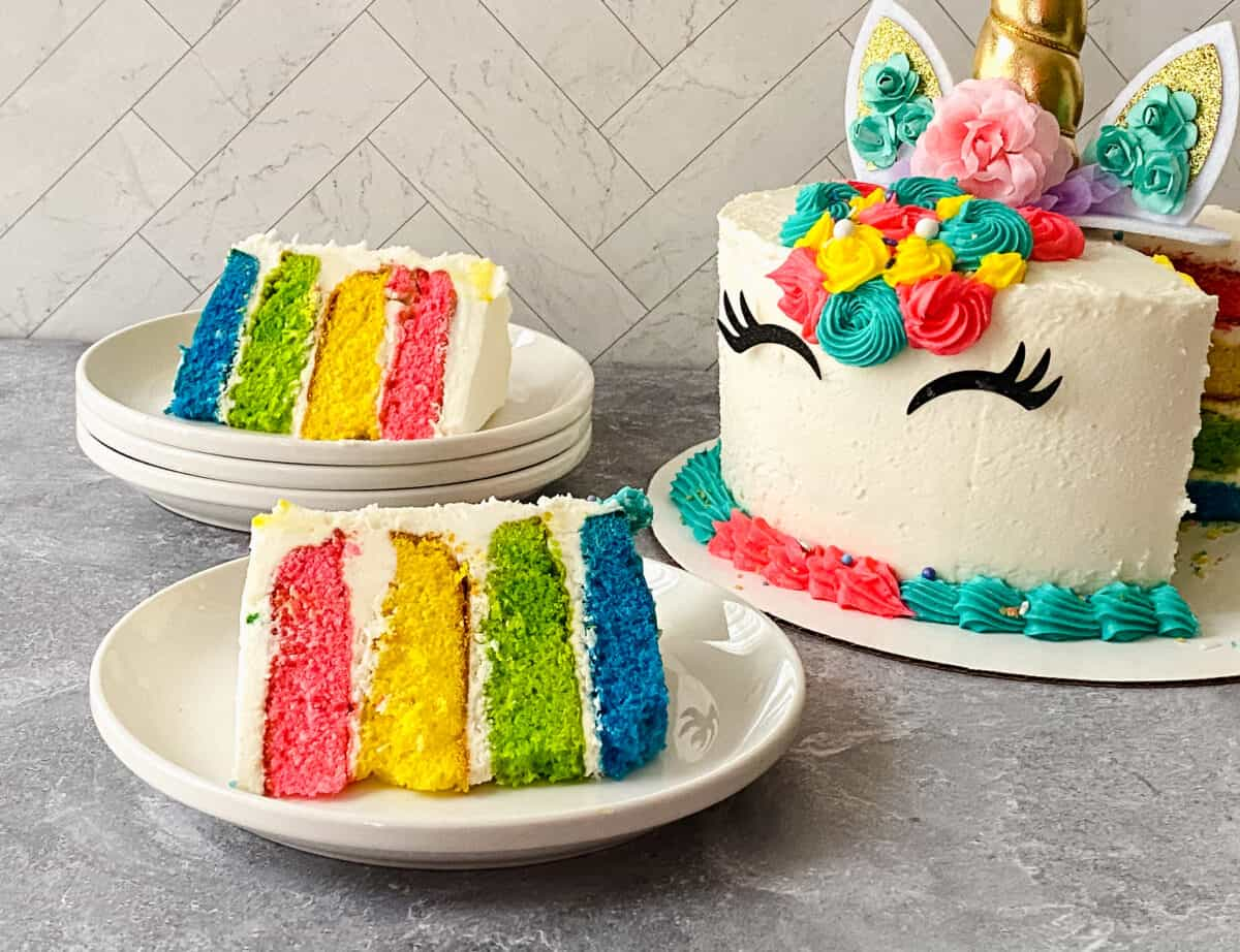 completed rainbow unicorn cake with two pieces sliced out and resting on plates so you can see the rainbow layers