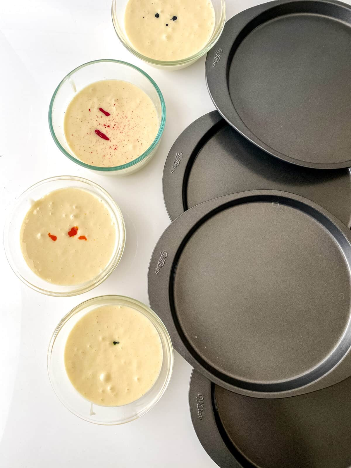 4 pans and four bowls of cake batter with food coloring in each one of them ready to be mixed