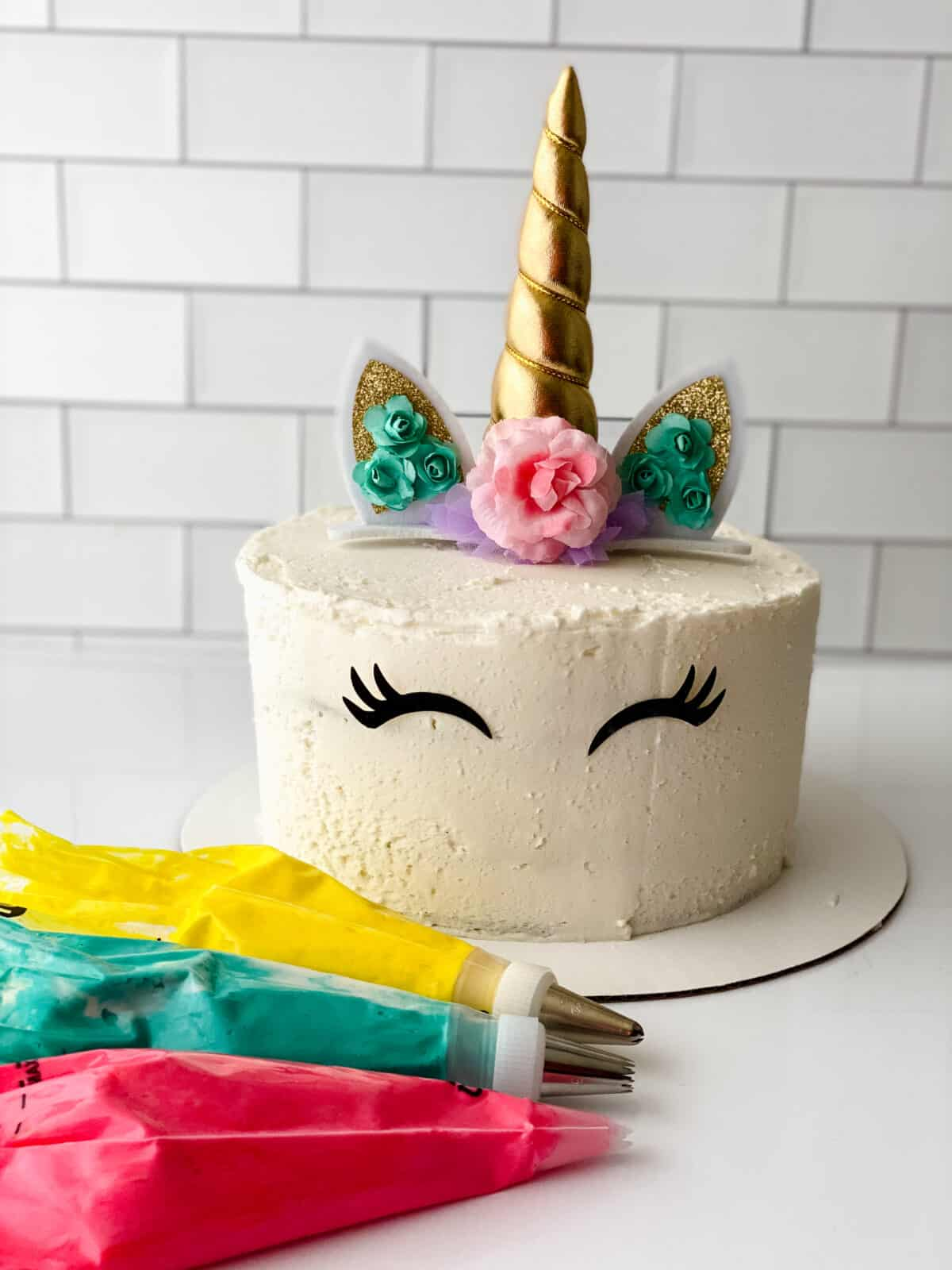 crumb coated unicorn cake with topper and eyelashes added. yellow, red, and teal icings are in frosting bags in the foreground