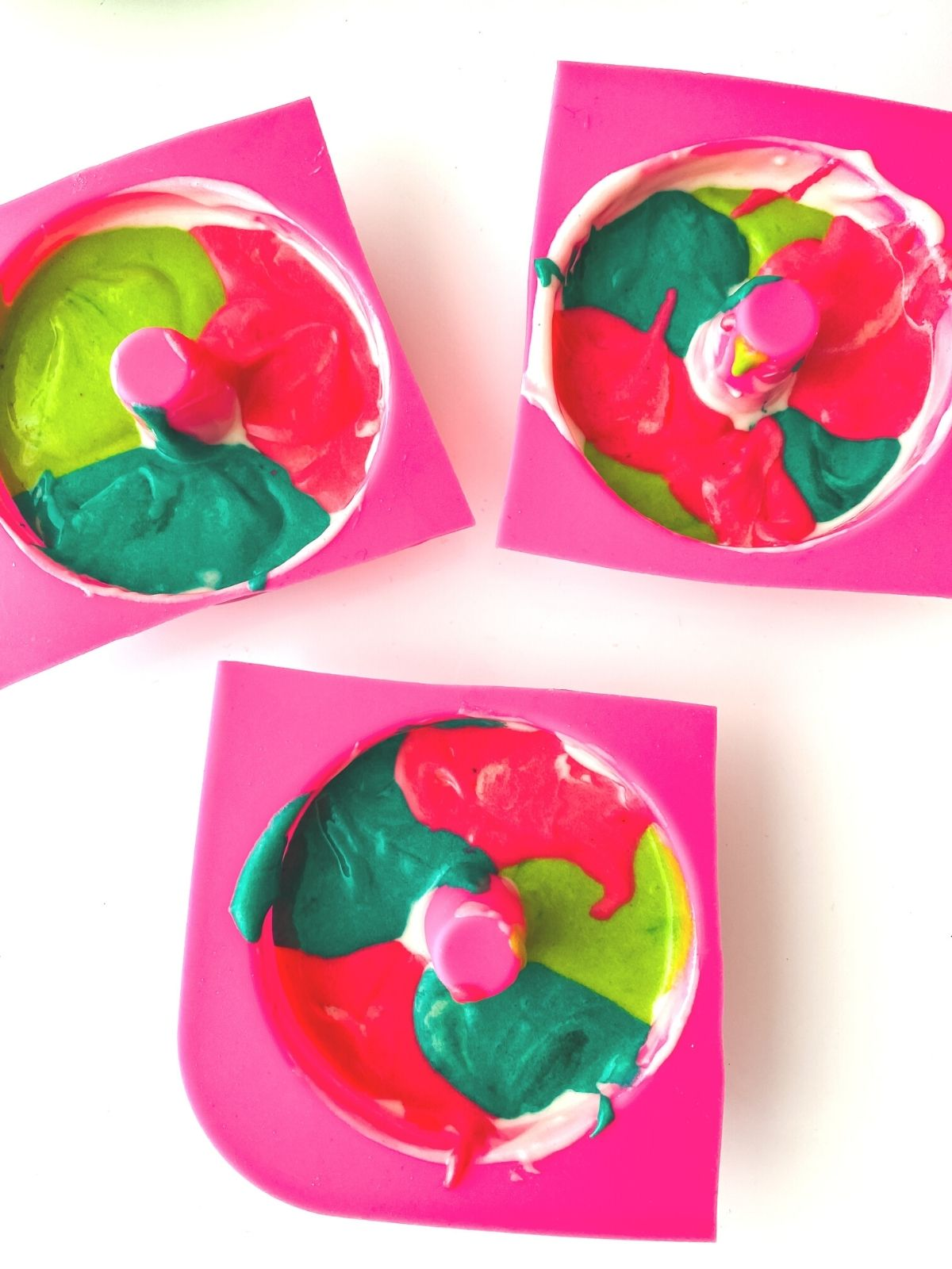 colored donut batter piped into pink silicon donut molds