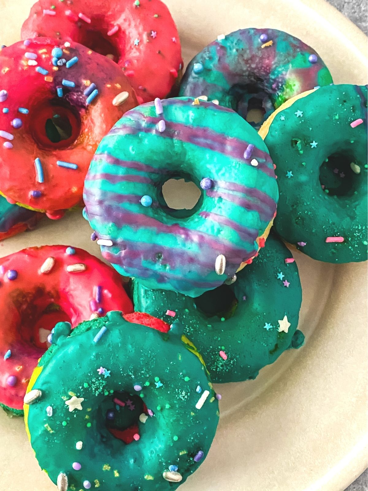a plate of multicolored rainbow unicorn donuts with stripes and sprinkles
