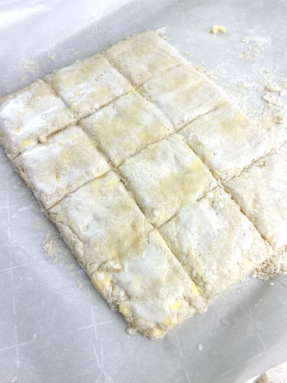 raw biscuit dough cut into 12 squares.