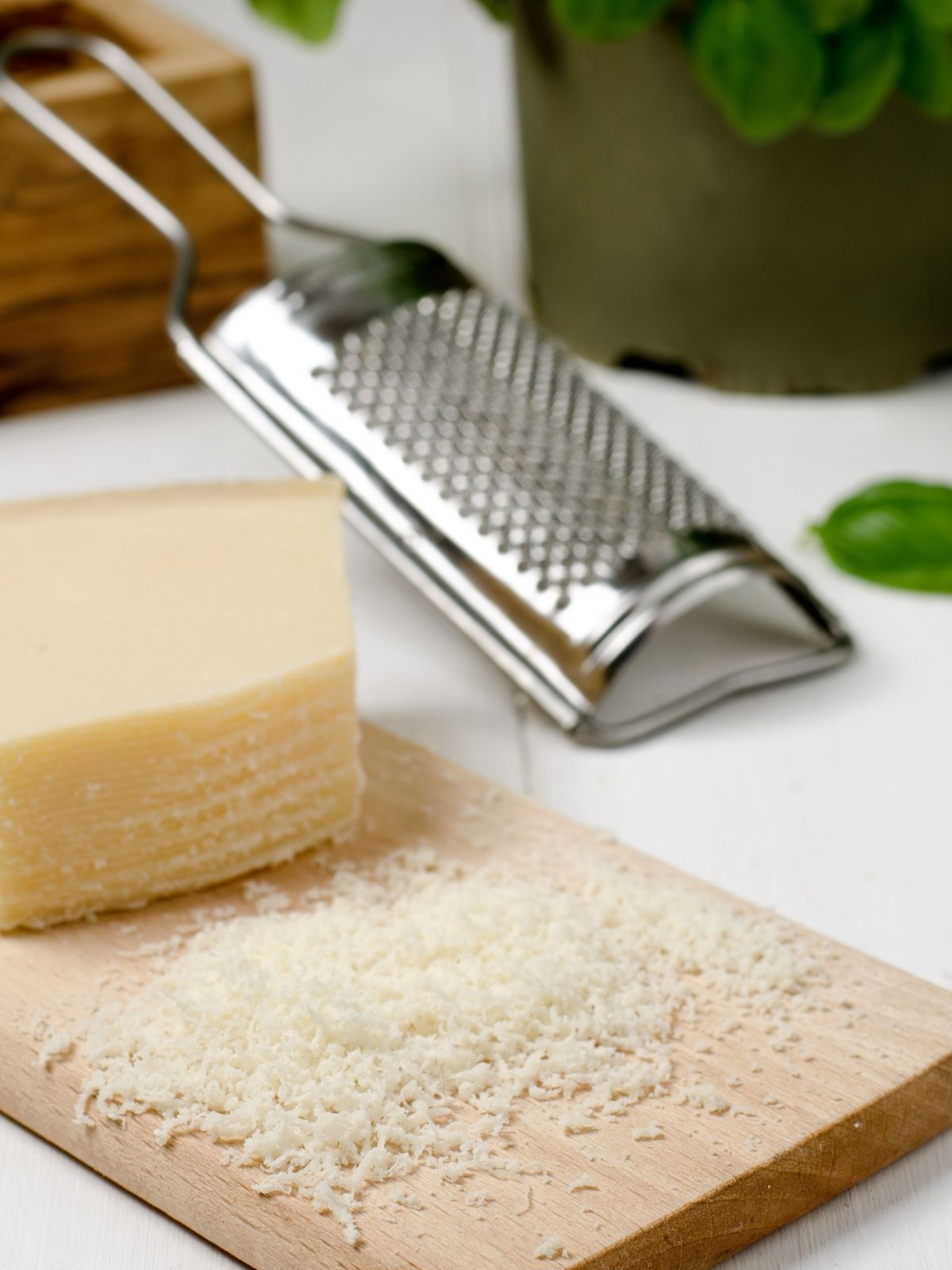 A block of parmesan cheese resting on a cutting board. Some of the cheese has been shredded in the foreground and a hand-held cheese grater is in the background.