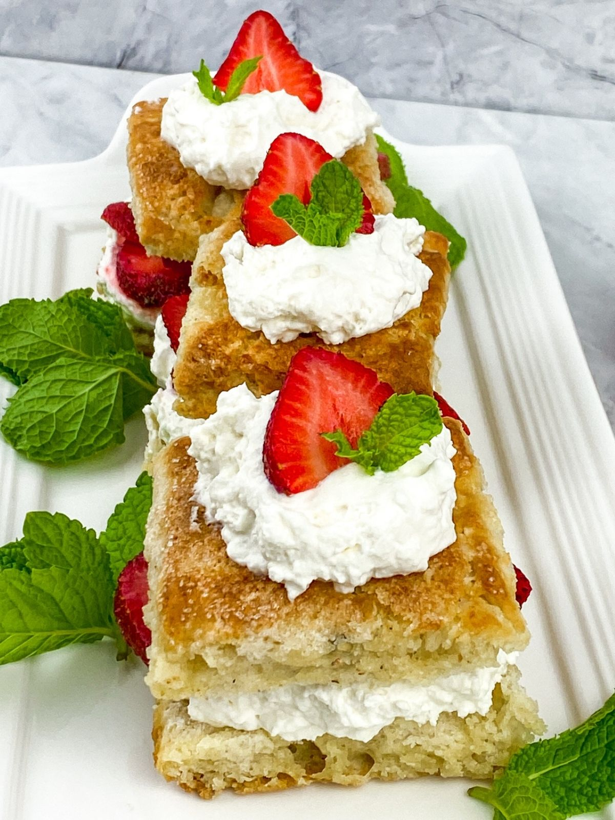 Three prepared strawberry shortcakes assembled and garnished with mint sprigs.