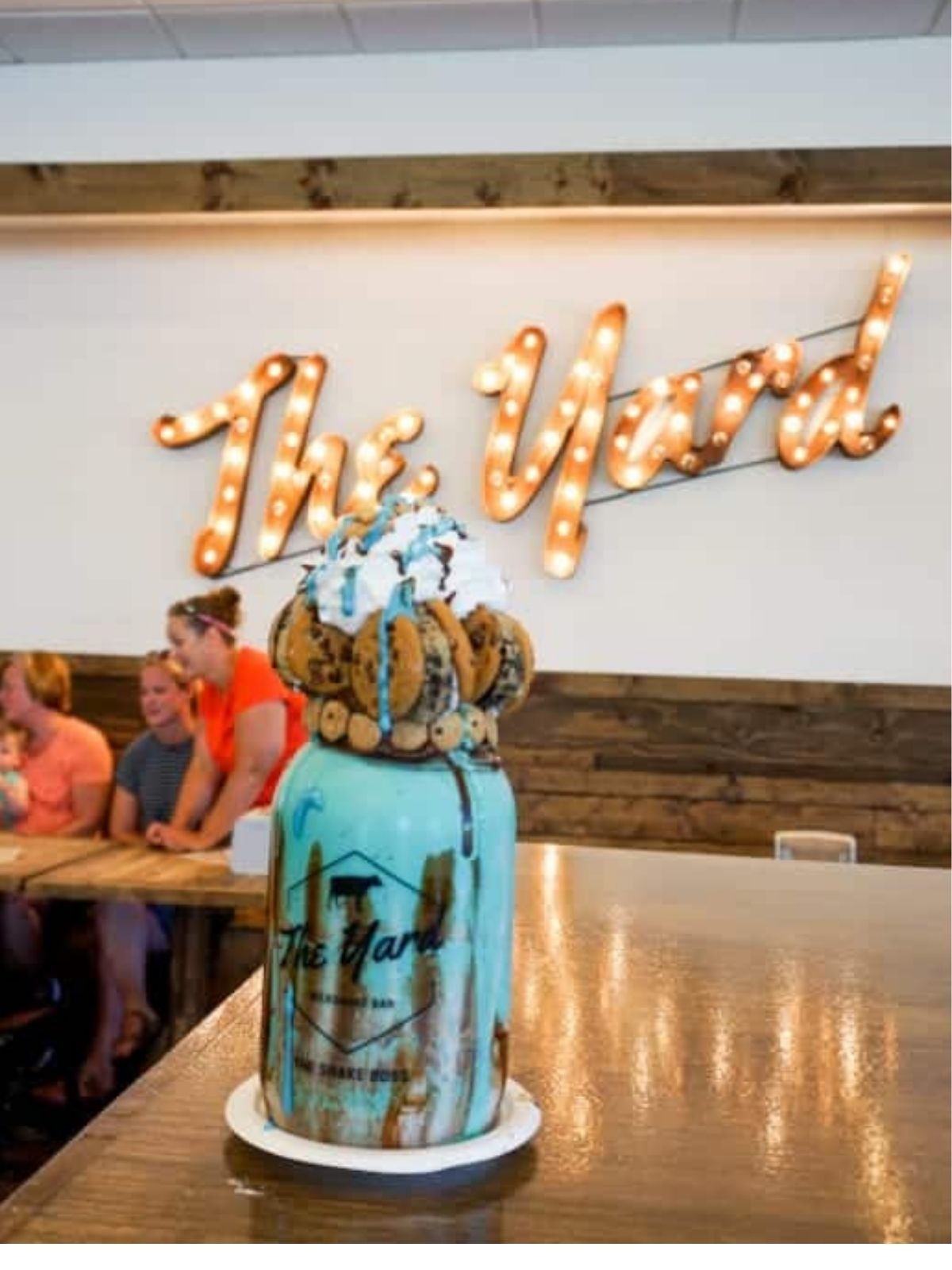 """the background is a sign that says """"the yard"""" in light up letters. the foreground is a blue cookie monster milkshake"""