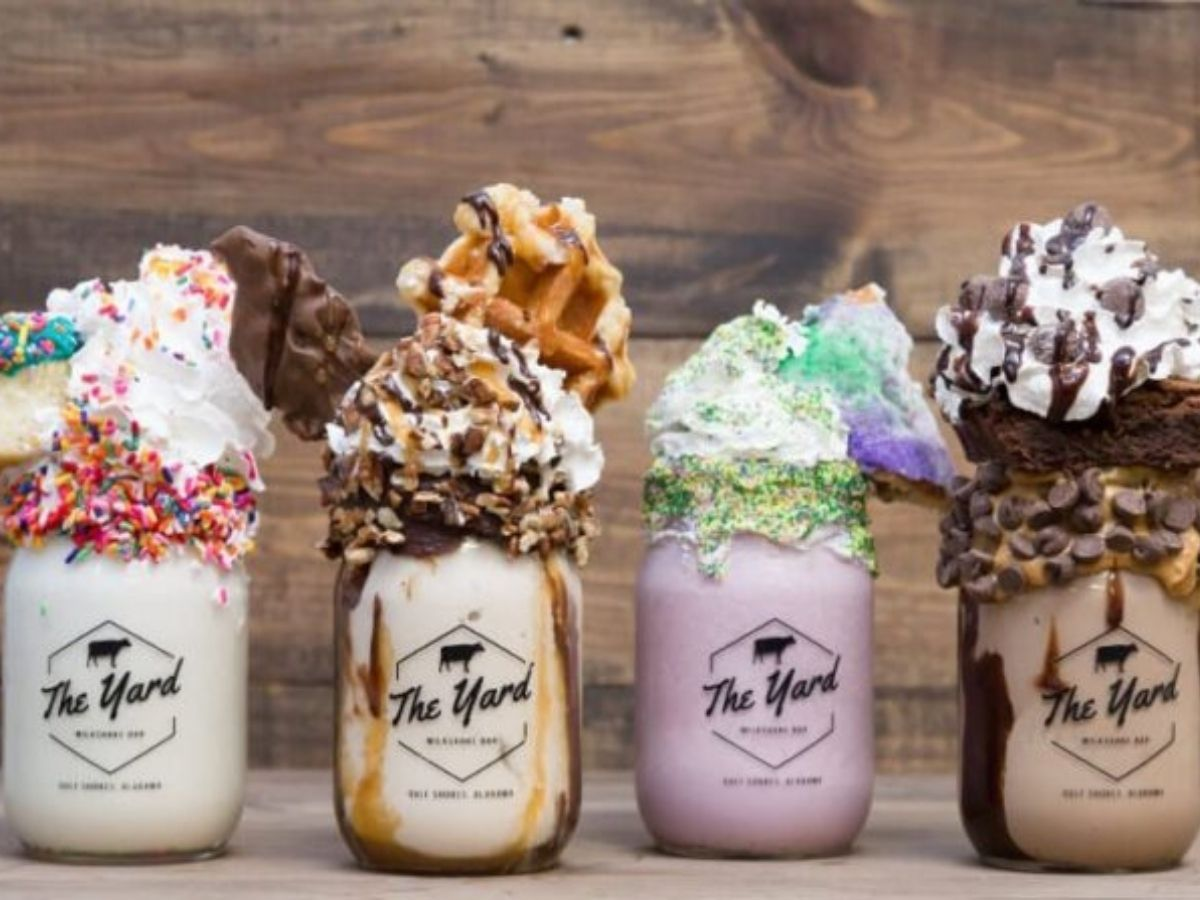 a lineup of four different milkshakes from the yard milkshake bar in Gulf shores, each served in a mason jar
