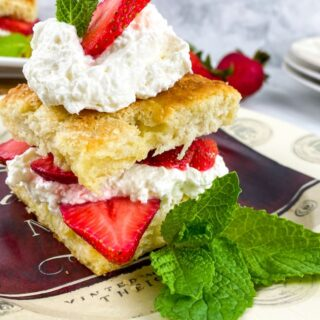 classic strawberry shortcake assembled with strawberries and whipped cream on a plate with a mint garnish.