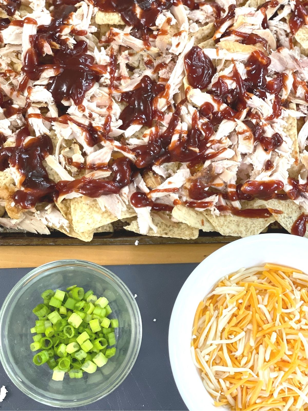 nachos topped with shredded chicken and bbq sauce.