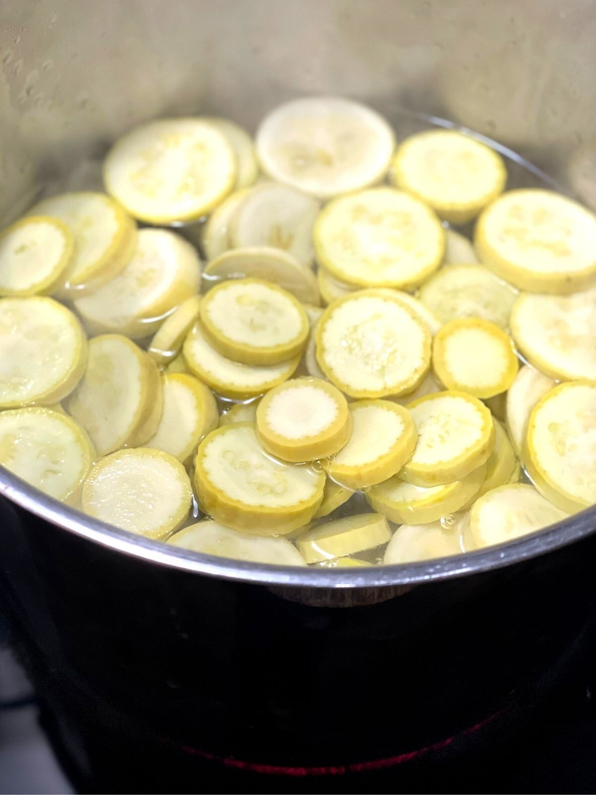 Squash slices being blanched in a large pot of boiling water.