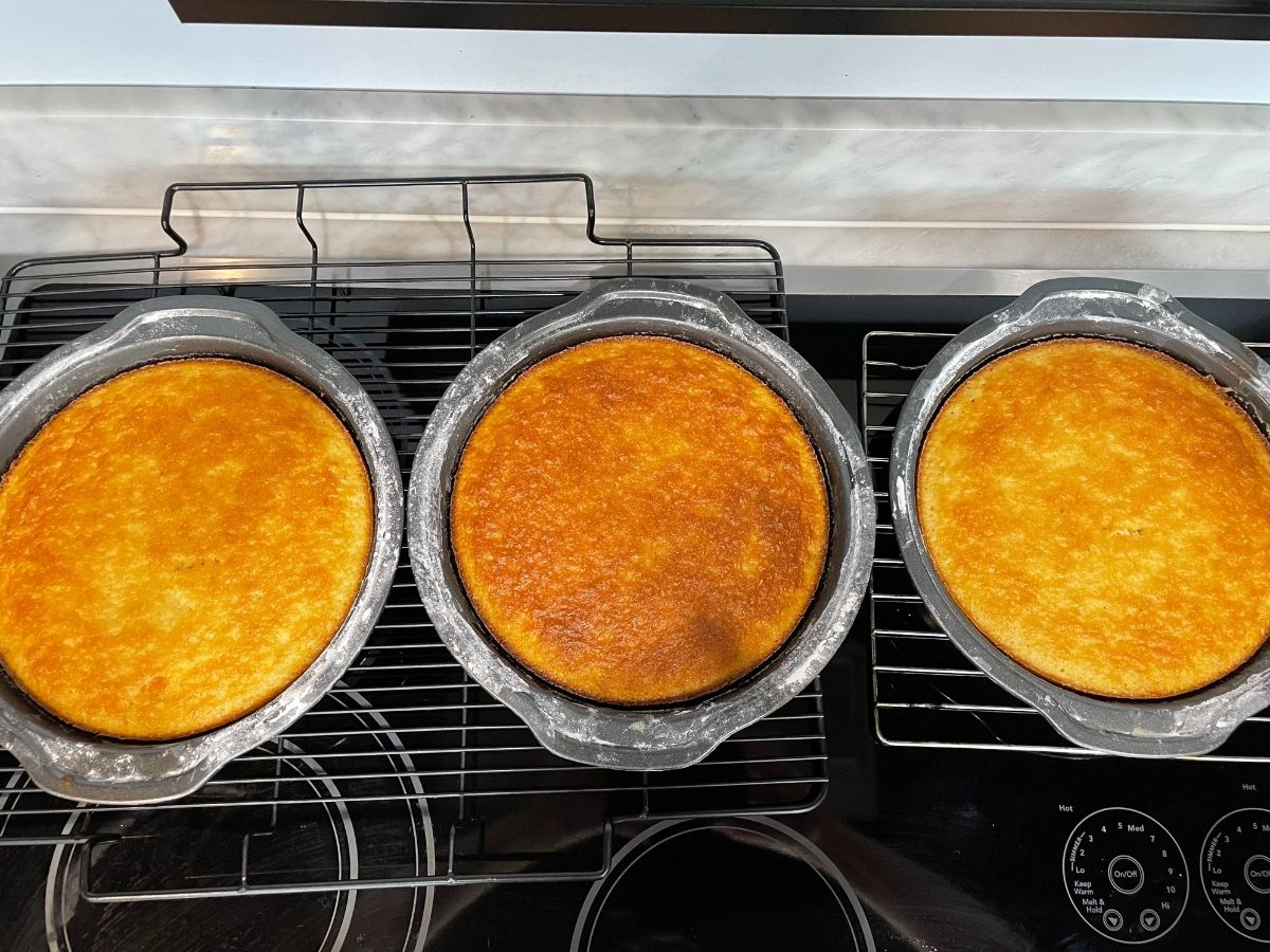 """Three 9"""" baked cakes resting on wire cooling racks"""