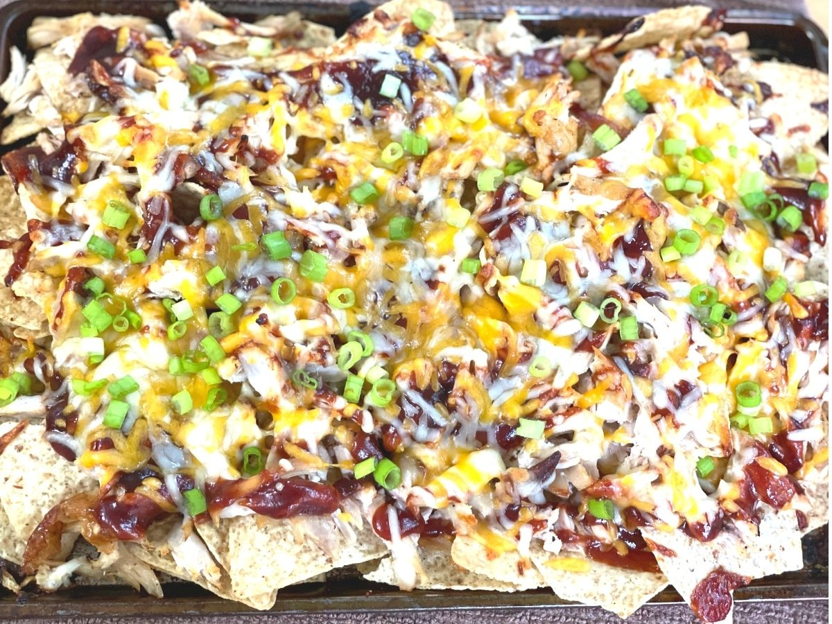 overhead shot of a full sheet pan of baked BBQ chicken nachos ready to serve.