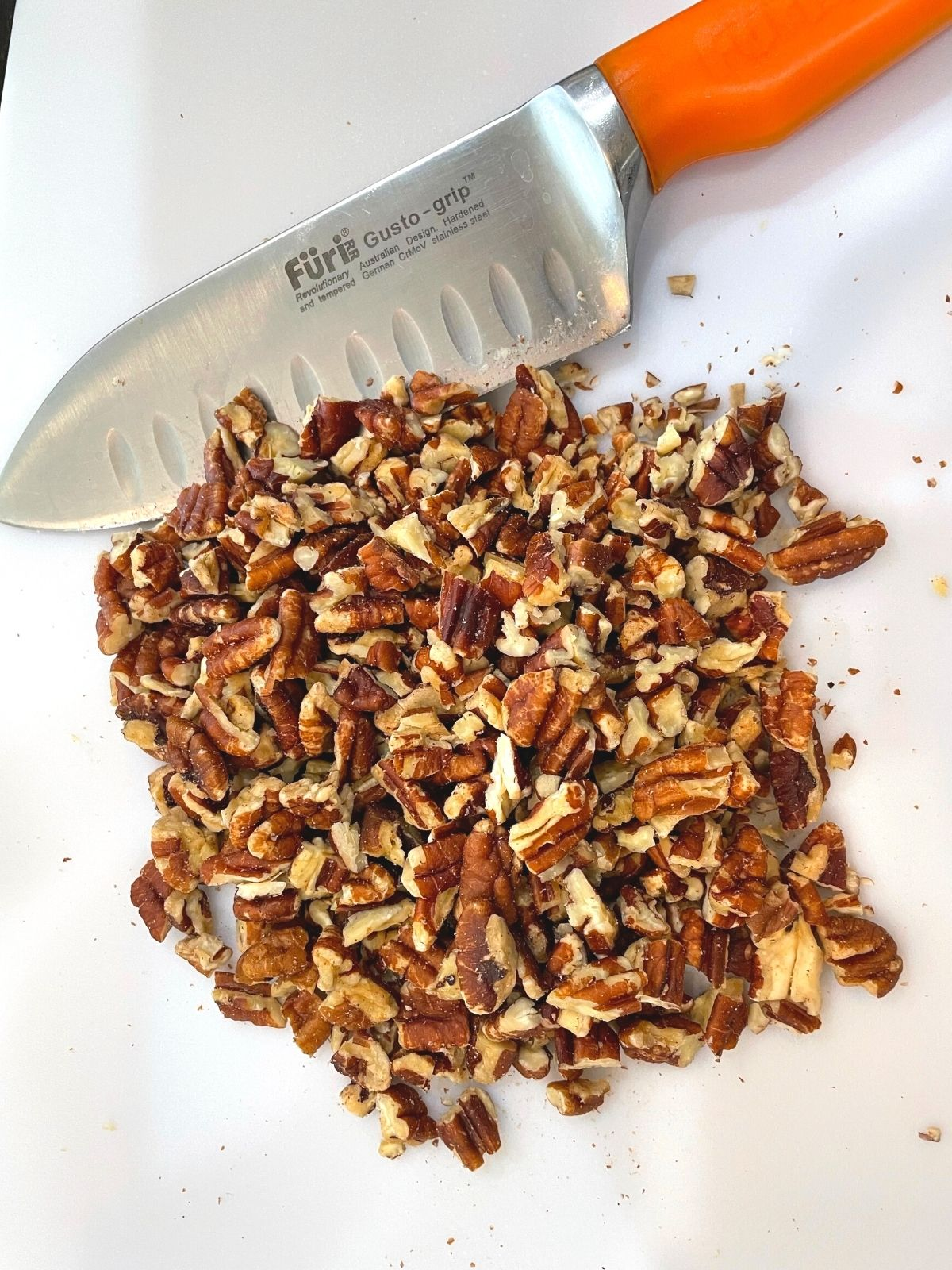 Chopped pecans on a cutting board with a knife.