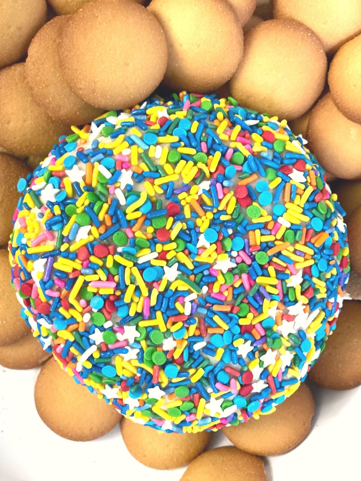 a sprinkle covered cream cheese ball surrounded by vanilla wafers and graham crackers for dipping.