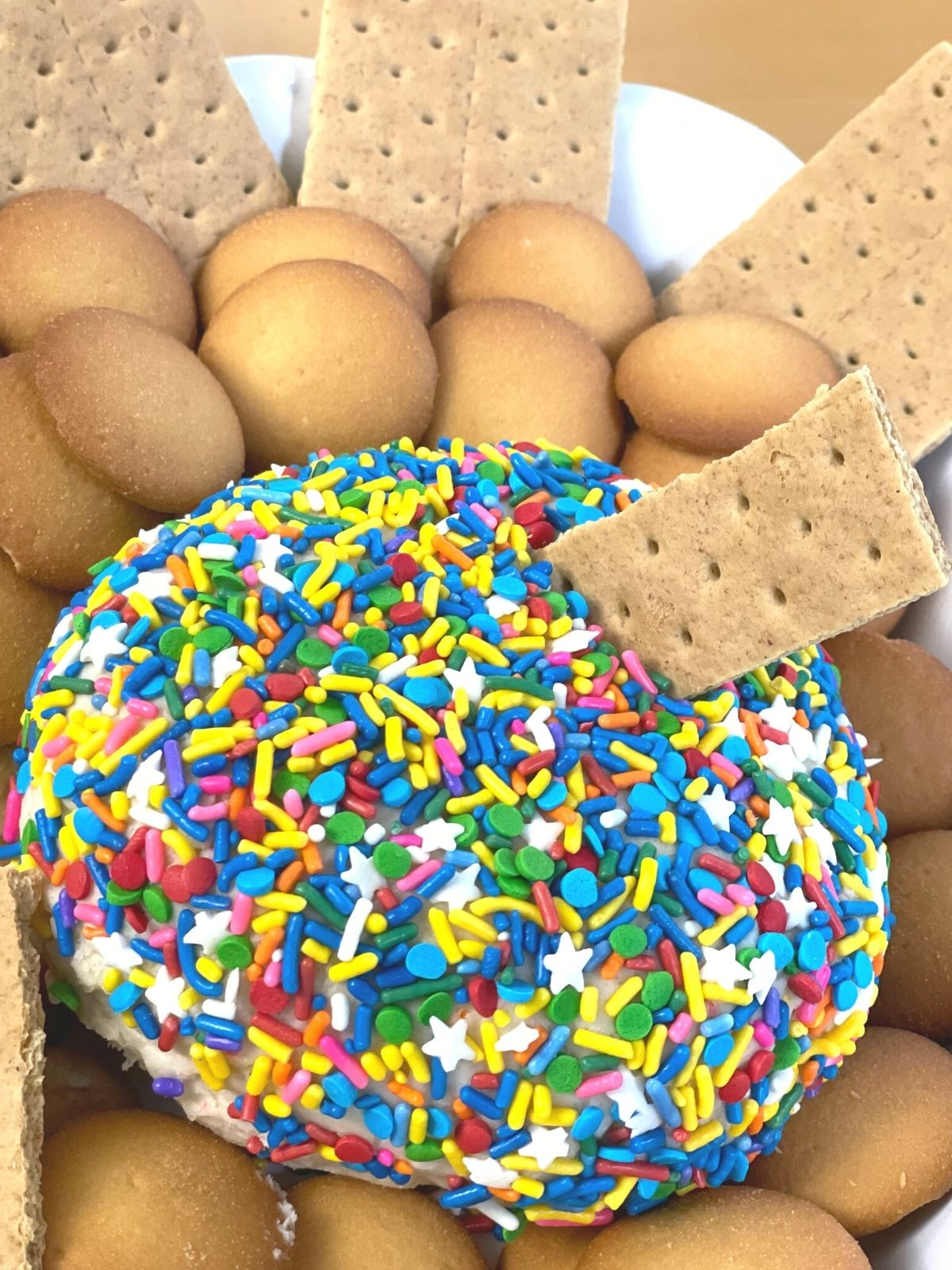 Finished funfetti dip cake mix dessert cheese ball with a graham cracker for dipping sticking out of it.