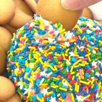 A funfetti cake dip rolled into a ball and covered in sprinkles to make a cake mix dessert served with graham crackers.