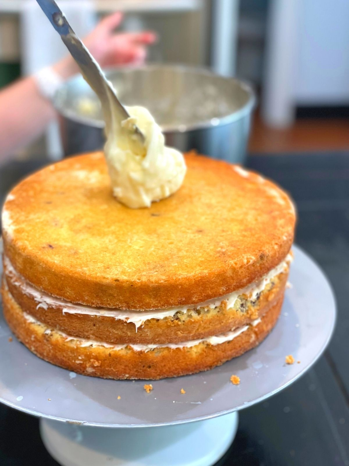 A three-layer cake ready to be frosted on the top and sides with an icing spatula.