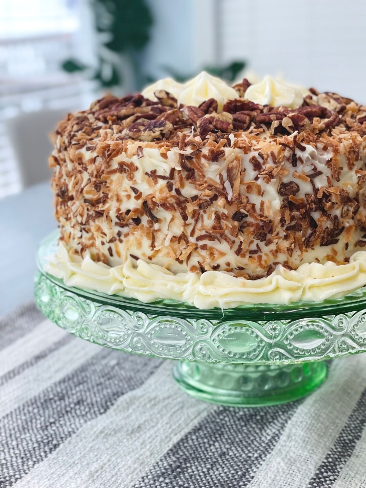 Round Italian cream cake covered in coconut and pecans on a vintage glass cake stand.