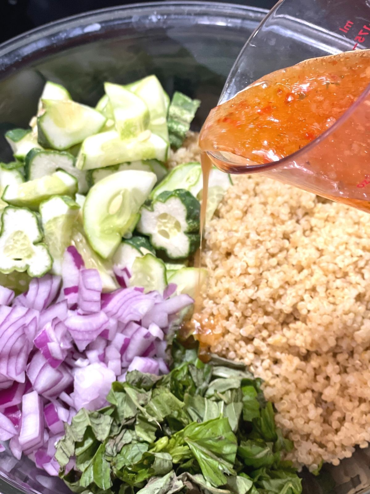 pouring italian dressing into a bowl of cucumber salad ingredients.