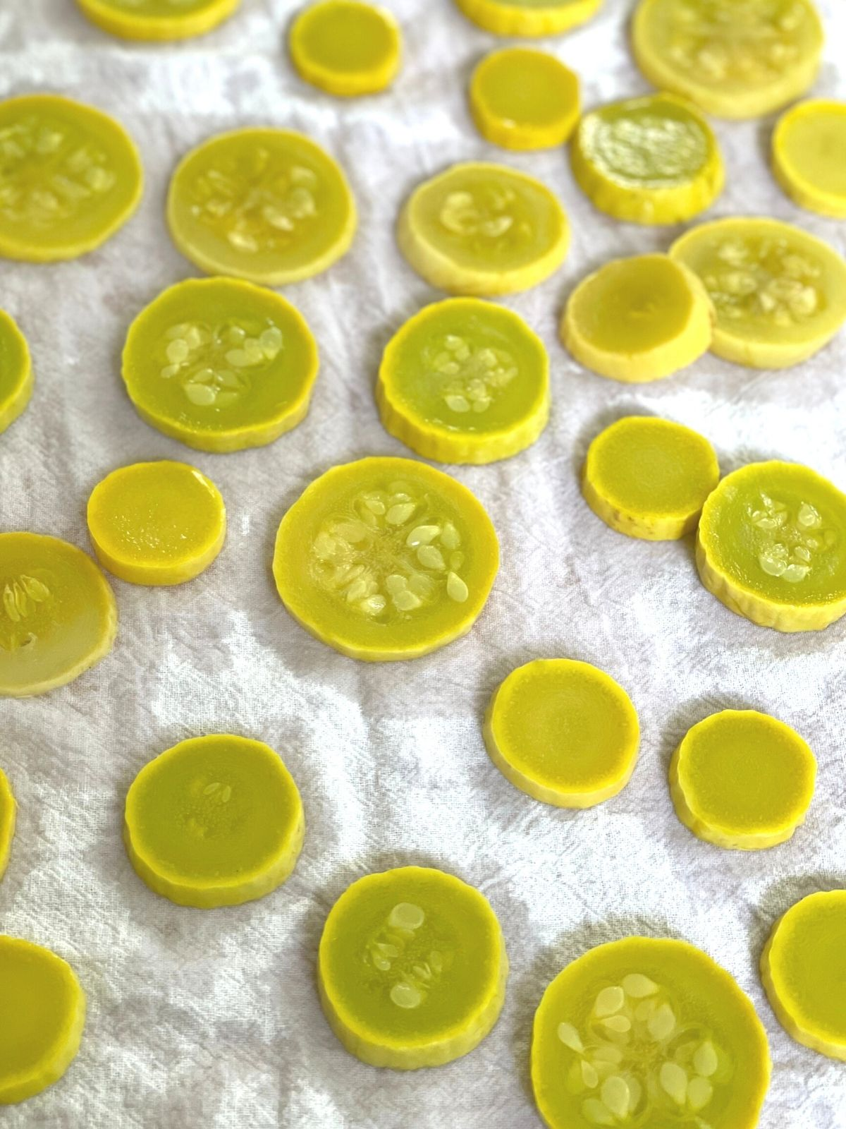 Blanched yellow squash slices drying on a tea towel.