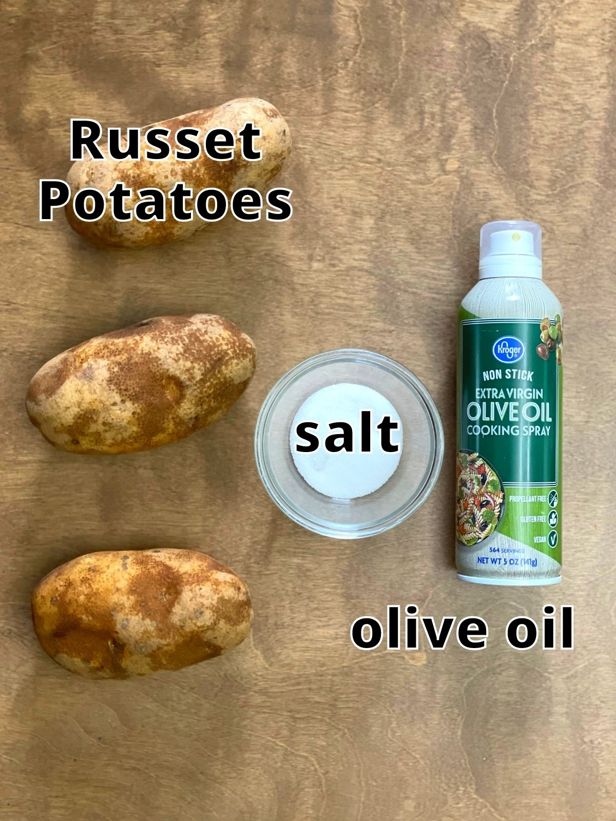Three Russet Potatoes, a bowl of salt, and a can of olive oil cooking spray.