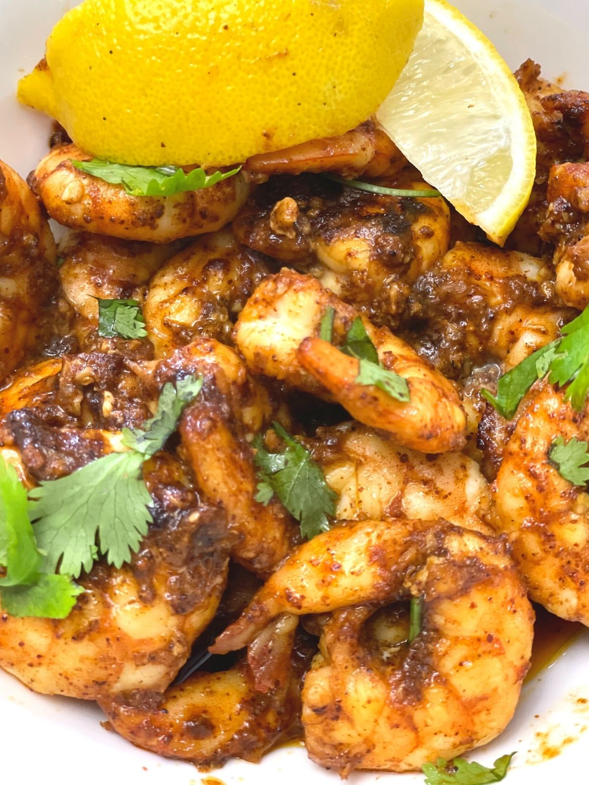 A close up of a bowl of blackened shrimp topped with cilantro. Lemon wedges are used as a garnish.