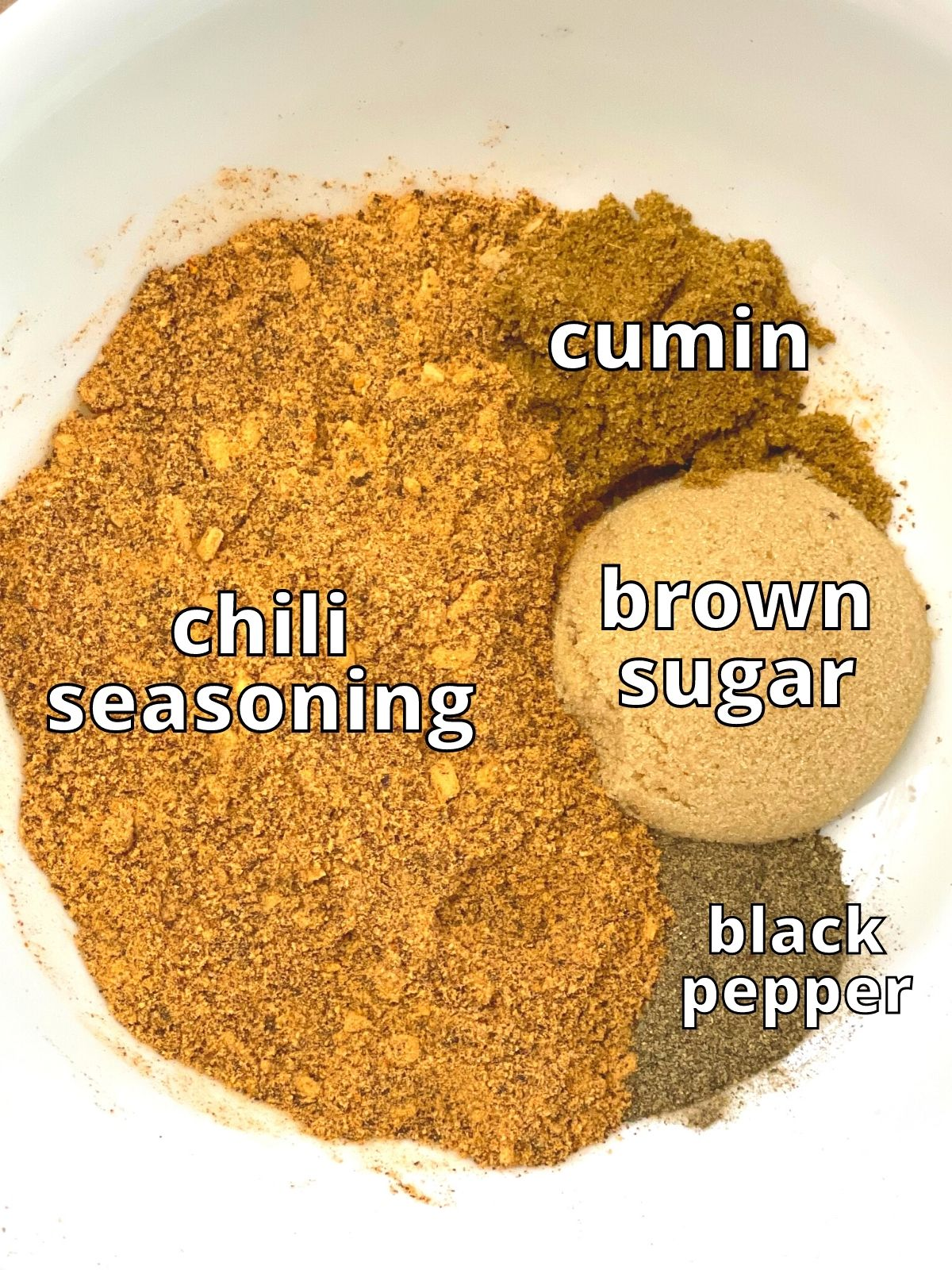 Blackened shrimp dry rub ingredients. Pictured is chili seasoning, cumin, brown sugar, and black pepper.