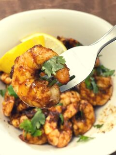 A bowl of blackened shrimp topped with cilantro. A fork is holding a single shrimp up to the foreground.