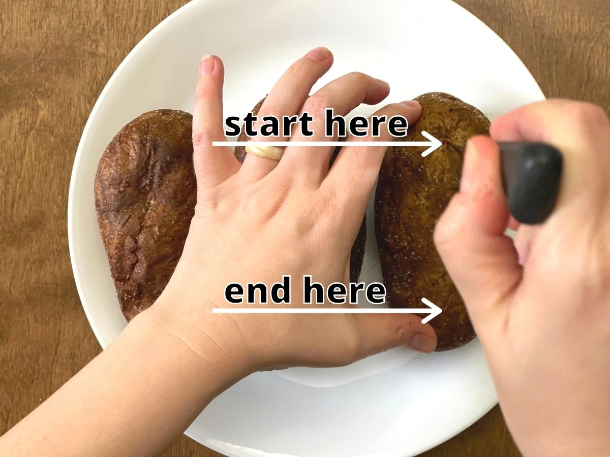 Hands cutting a baked potato for serving. Arrows show where to start the slice and where to end it.