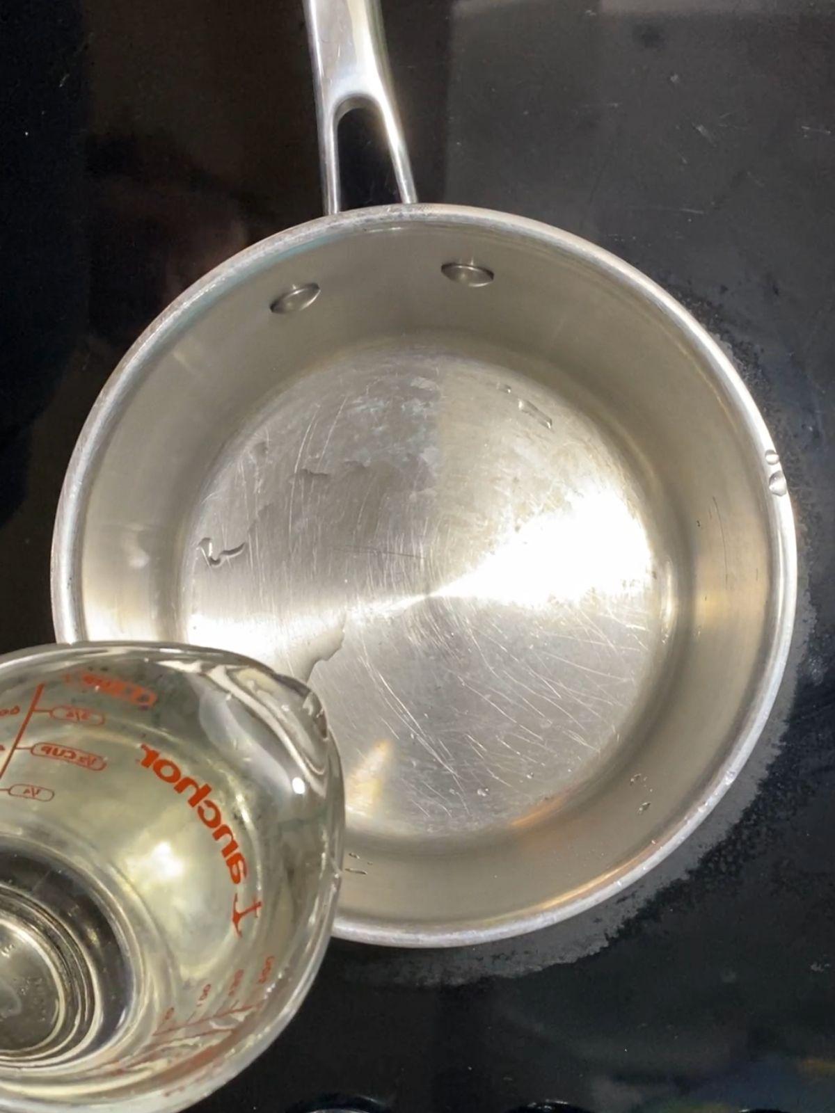 adding corn syrup to a saucepan.