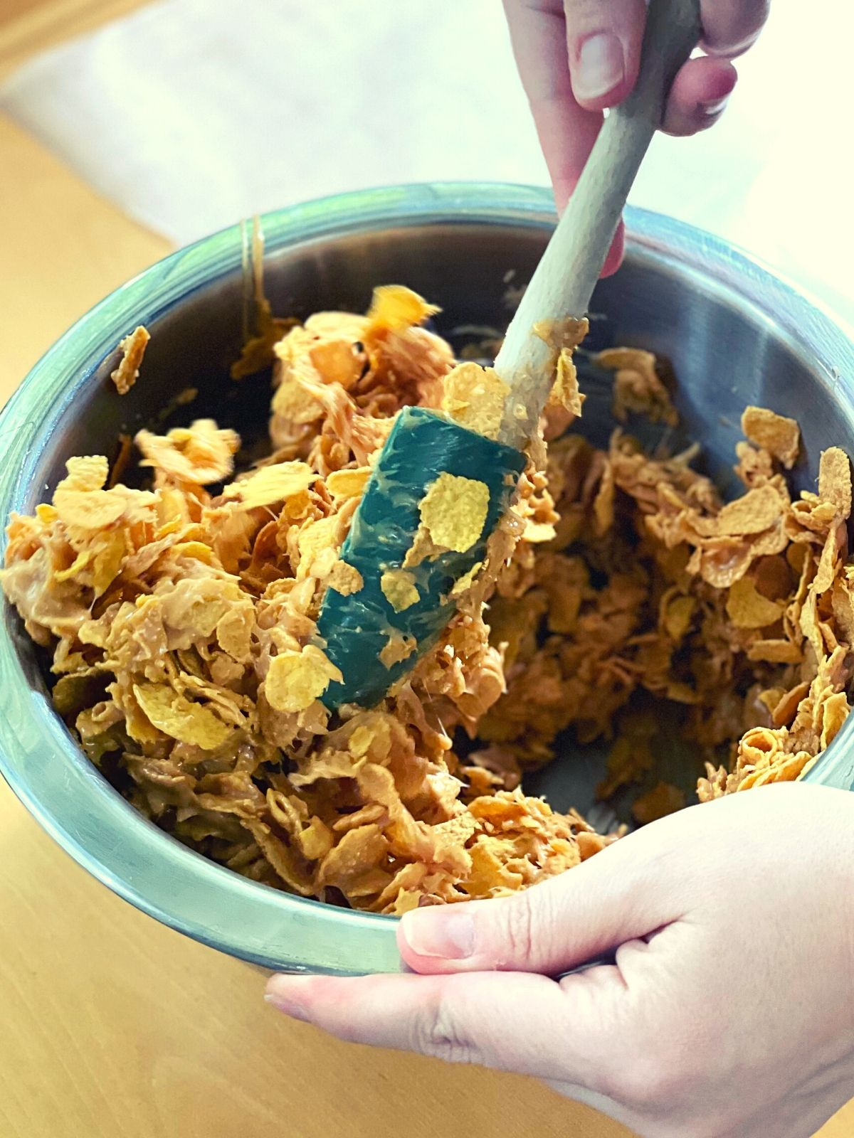 Using a green spatula to mix the peanut butter mixture into the cornflakes in the large mixing bowl.
