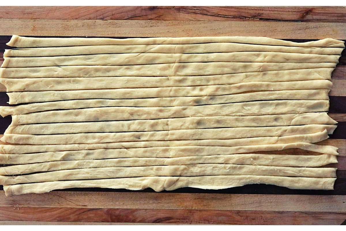 Raw crescent roll dough sliced vertically down the rectangular shape to make long, skinny strips of dough.