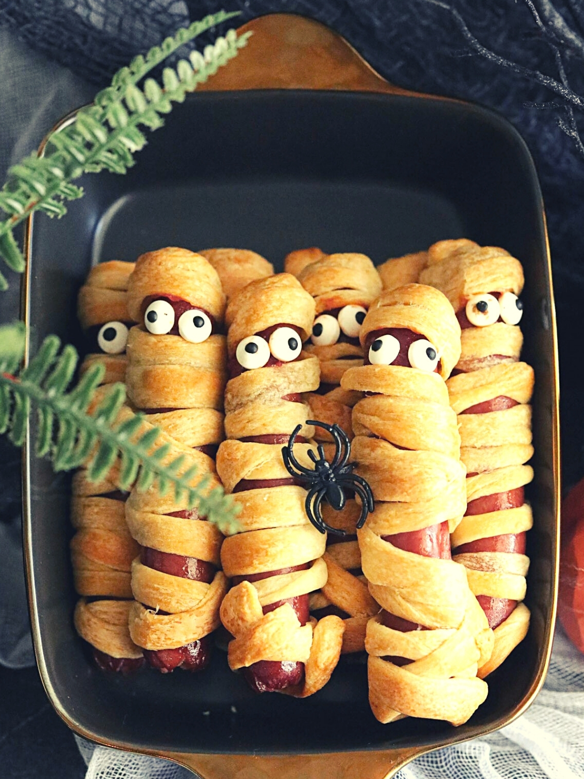 Eight hot dog mummies with candy eyes nesting in a black bowl for Halloween.