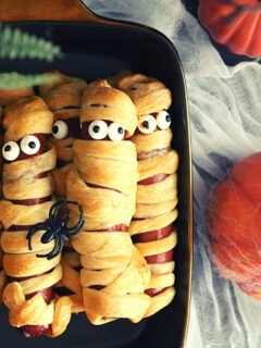 halloween mummy hot dogs with candy googly eyes nested in a black, square bowl. Pumpkins are in the background for spooky decor..